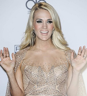 Carrie Underwood leaps to defence of personal trainer