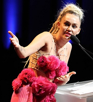 Miley Cyrus licks piano for charity auction